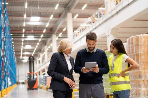 Two managers and a warehouse worker look at current inventory on a tablet