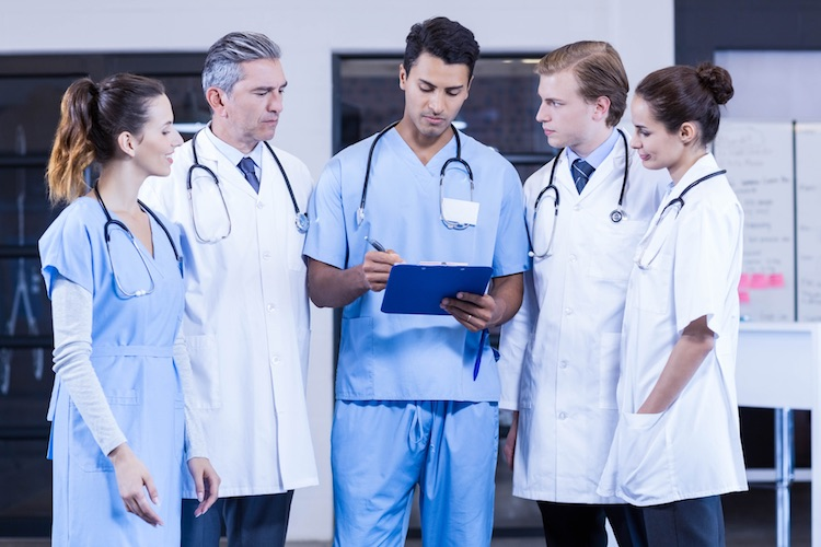 Director of Nursing consulting with his team while reviewing report on a clipboard