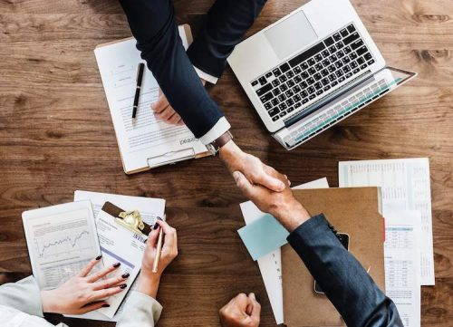 Project managers in business attire shake hands at a table with stacks of schedules, contracts, and invoices.