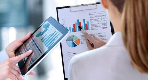 business colleagues working and analyzing financial figures on both a tablet and clipboard