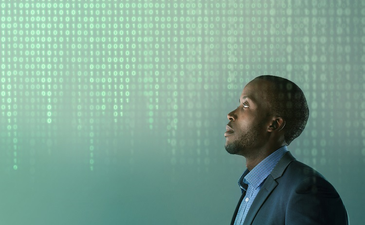 A man in a suit jacket looks up at a grid of digital binary numbers