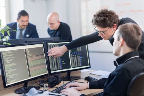 Two information assurance engineers review software code on a screen.