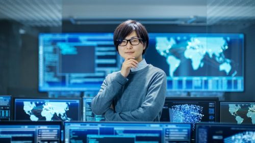 A chief security officer stands in a room surrounded by monitors and large screens of geographical locations.