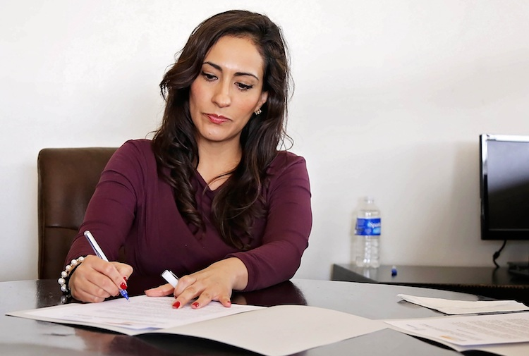 A private practice health manager sitting at table fills out paperwork in a folder.