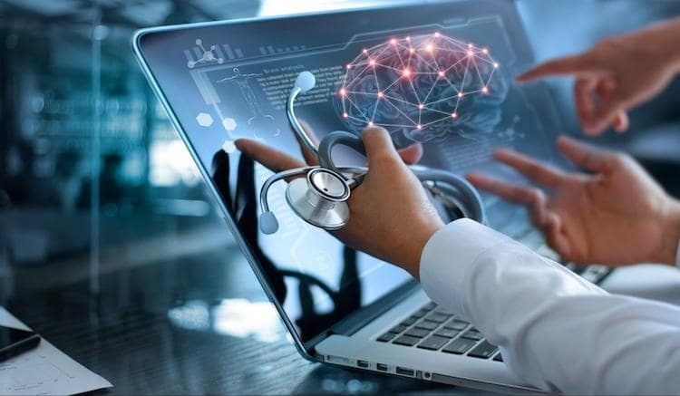 Doctor in a white coat holds stethoscope up to laptop that is displaying an image of a brain model