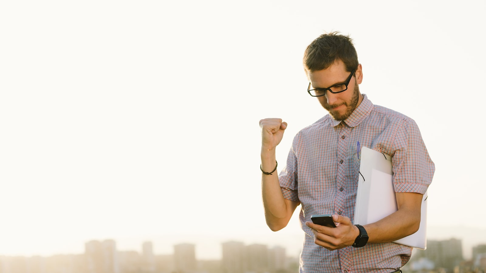 Working professional carrying documents outdoors pumps his fist while looking at a smartphone