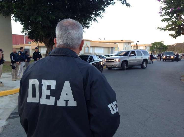 A DEA agent stands facing other agents and vehicles in a parking lot.