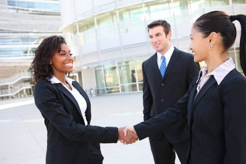 Sales professionals meet outside of office building and shake hands