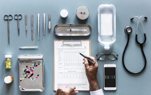 A close-up of hospital amenities, including a syringe, medical tools such as a stethoscope, IV bag, and medications, a cell phone reading the time, and a daily report schedule. A person is about to write on the schedule.