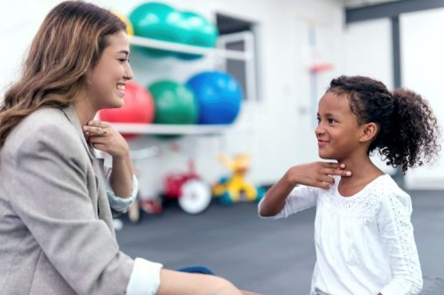 A speech pathologist and a young client do a language exercise.