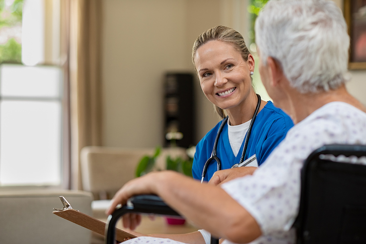 A public health nurse kneels down with an elderly patient in a nursing home while smiling and holding a clipboard.