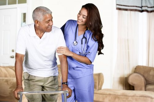 A female nurse assists an elderly male resident in an assisted living center