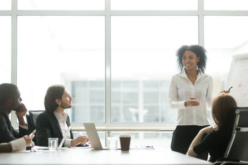 A female business leader presents to colleagues in a conference room