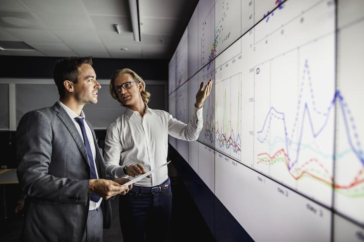 2 men in front of a whiteboard looking at graphs