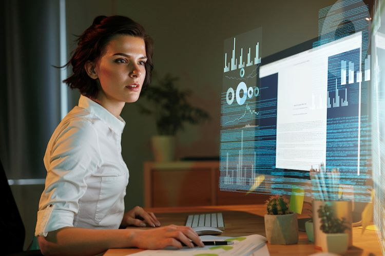 Female data scientist analyzing a computer screen with data visualizations.