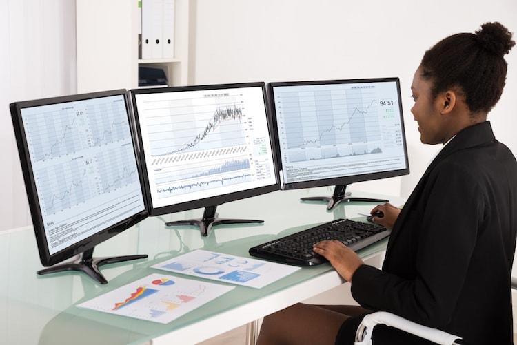 Female data scientist studies business data graphs.