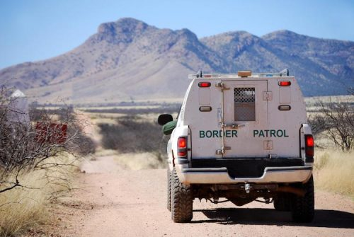 A CBP officer patrols a road near the border in a CBP vehicle.