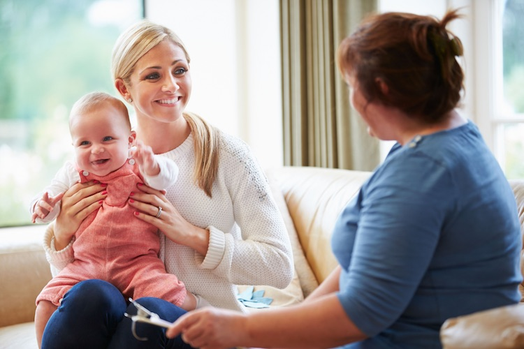 Mother holding her toddler while speaking to a home health manager