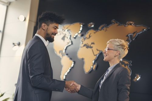 Two international marketing executives shake hands in front of a world map