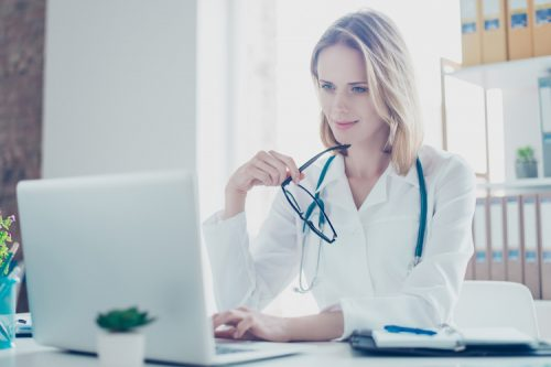 A health information manager works on a laptop at her desk while wearing a white coat.