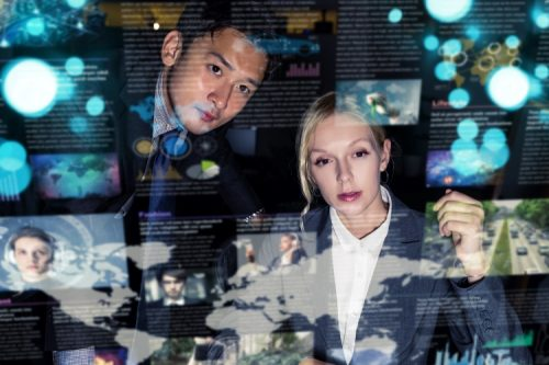 Two business professionals look at futuristic digital displays projected in front of them.