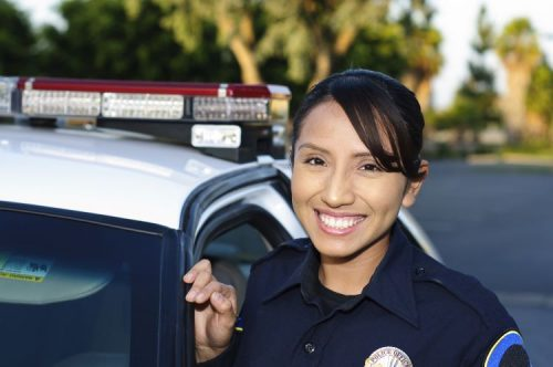 A smiling police officer stands beside her patrol car..