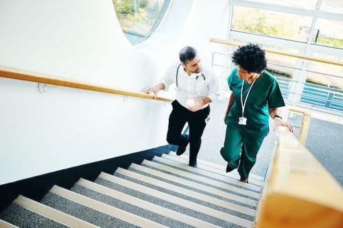 Doctor walks alongside nurse up a staircase while having a conversation