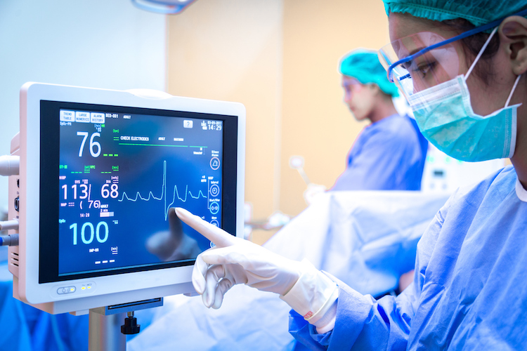nurse in intensive care unit monitoring patient heart rate during surgery