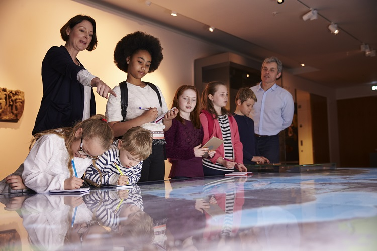 A historian shows a group of children a display during a tour of a museum.