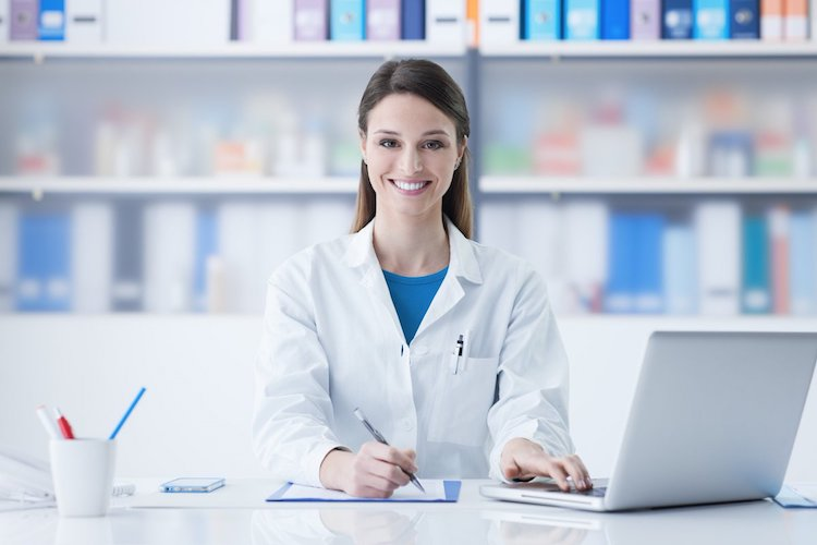 nurse in white coat smiles as she poses working on laptop