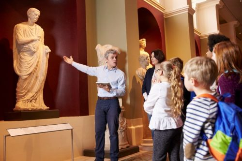 museum guide speaks to a group of children while pointing at a statue