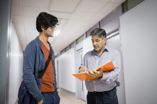 A university registrar meets with a student in a hallway to discuss course schedules.