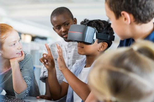 A group of students gathers around to observe their classmate wearing a pair of virtual reality goggles.