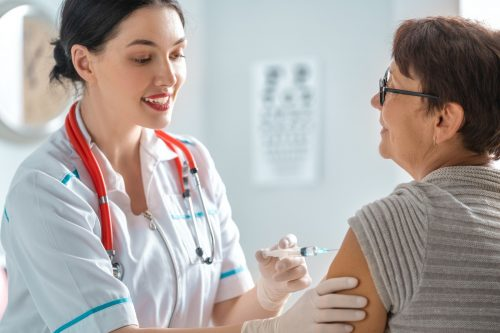 A public health nurse gives a shot to a patient.