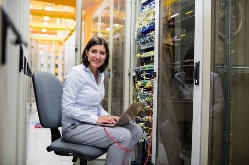 A network architect works on her laptop in a server room.