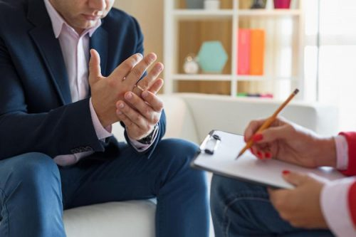 Psychiatrist evaluates patient during therapy session while taking notes.
