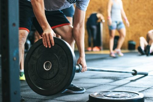 Image of a man in a gym connecting barbell to weight