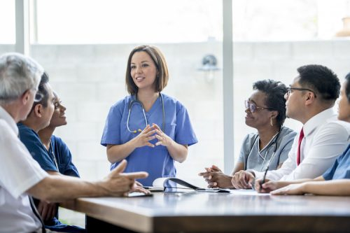 A nurse practitioner conducts a meeting for healthcare workers.