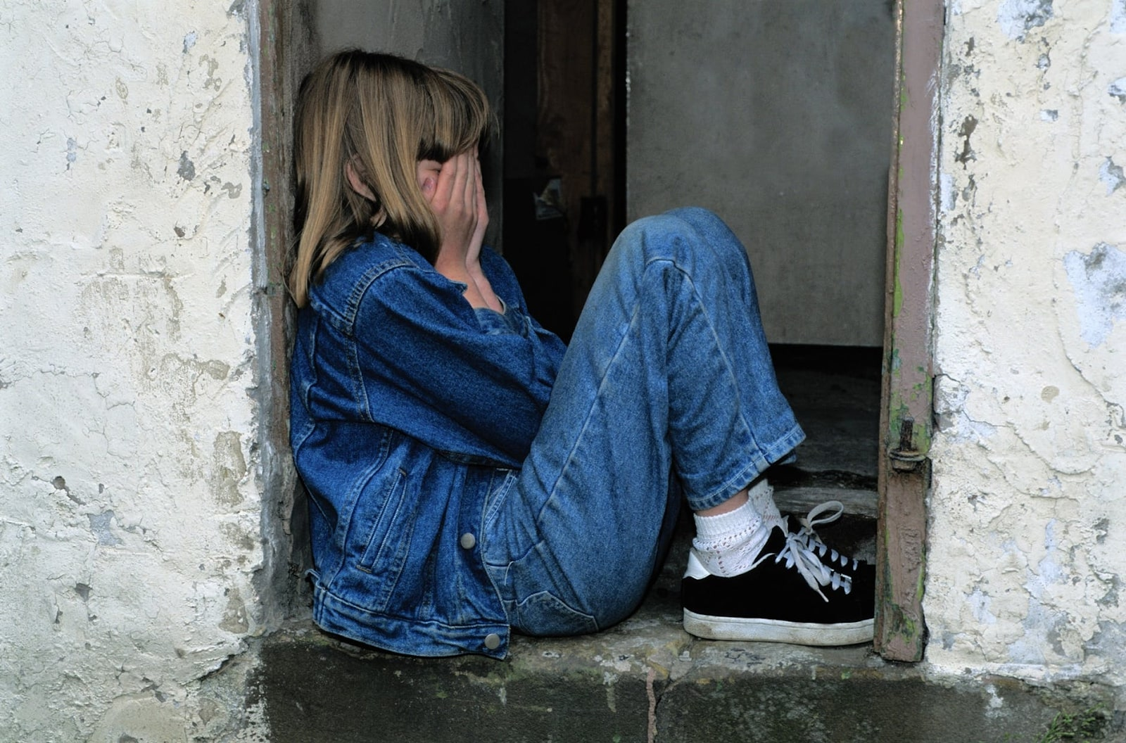A concept photo of loneliness, showing a young girl from the side, wearing denim and covering her face, sitting in a small alcove.