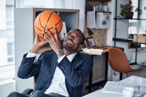 A businessman holds up a basketball while sitting at a desk in an office