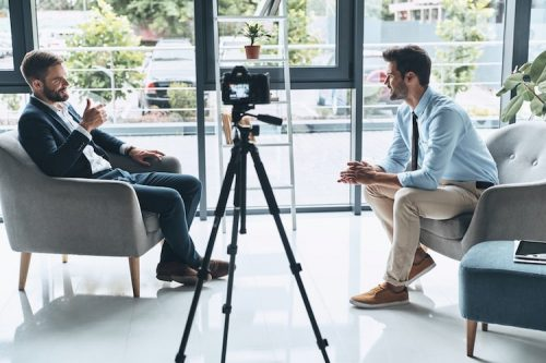 A journalist conducts a video interview for his podcast.