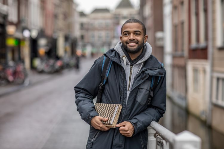 An international studies professional walks down a city street carrying two books.
