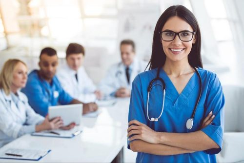 nurse with glasses smiling while standing in front of other healthcare professionals