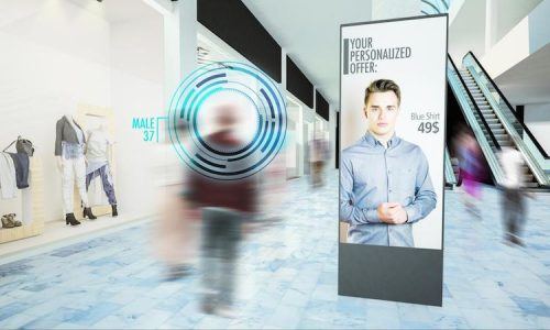 A shopper walks past a personalized digital display of a men's shirt advertisement at a mall.
