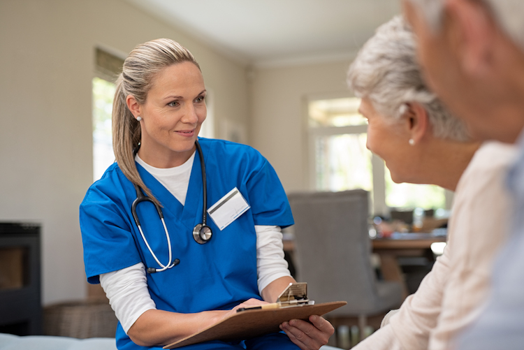 A female nurse in blue scrubs holding a clipboard sits down with elderly couple.