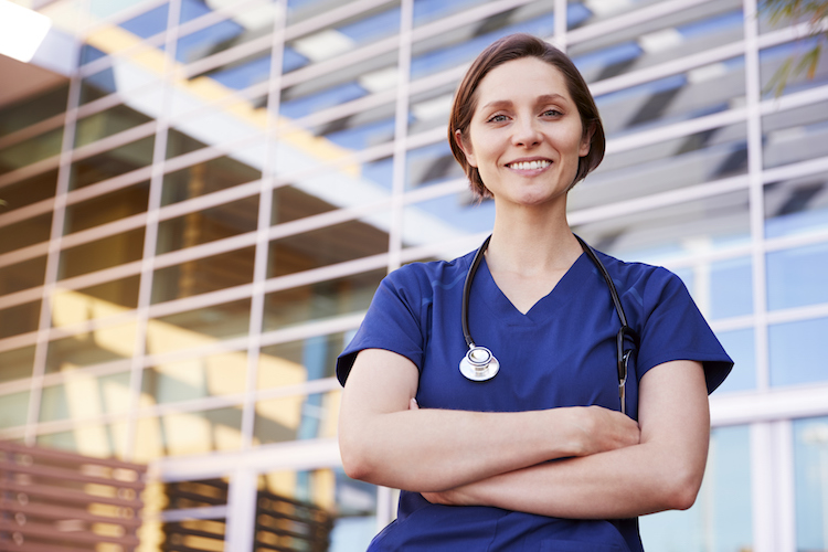 Nurse stands in front of a building wearing her blue scrubs and crossing her arms while smiling
