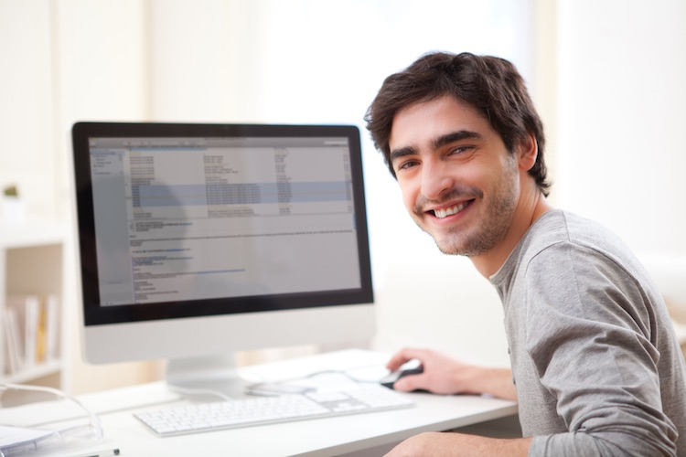 a smiling man sits at a desk with a computer in front of him