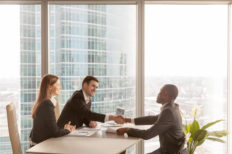 An HR professional shakes hands with a job applicant in an office with a view of the city.