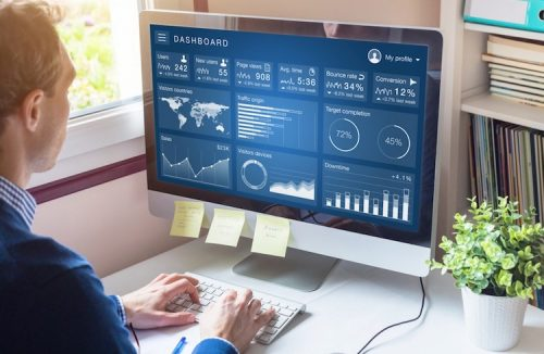 A professional digital marketer reviews analytic dashboard that displays website metrics.