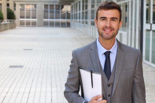 professionally dressed man carrying a folder stands outside an academic building